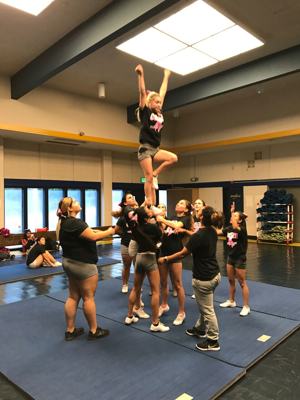 The Cheer Team practices a stunt.